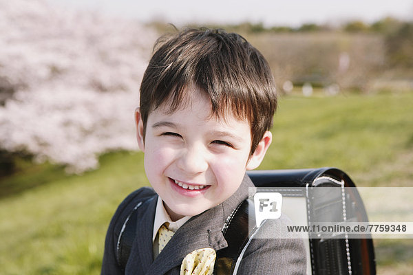 Young boy in a school uniform smiling at camera