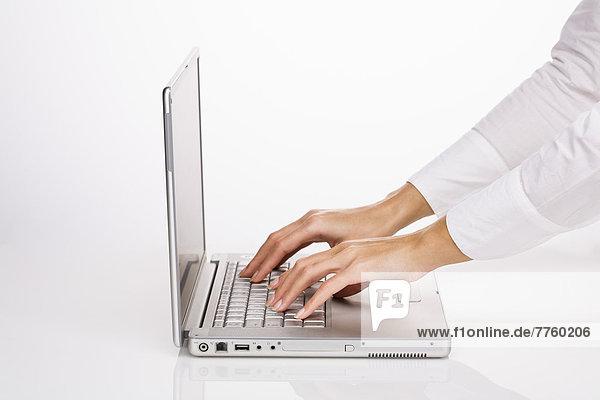 Frauenhände beim Schreiben auf einem Laptop