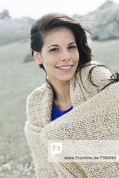 Junge Frau mit Schal am Meer