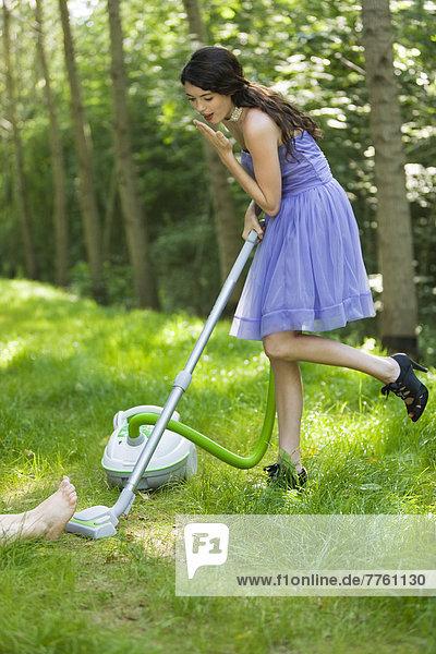 Junge Frau beim Saugen von Gras