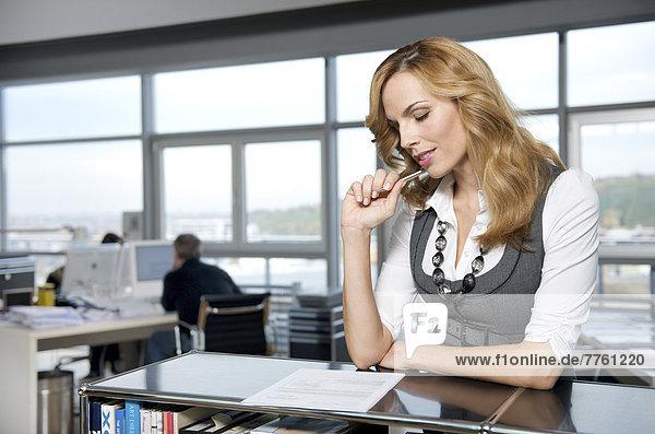 Geschäftsfrau beim Ausfüllen eines Papiers