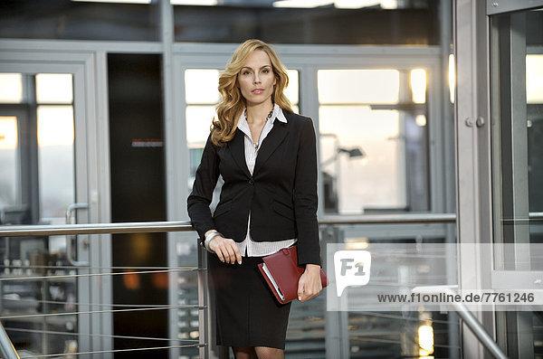 Geschäftsfrau  die sich gegen das Geländer lehnt
