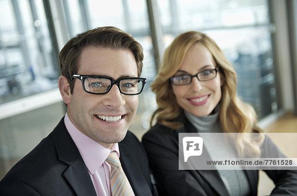 Geschäftspaar lächelt vor der Kamera