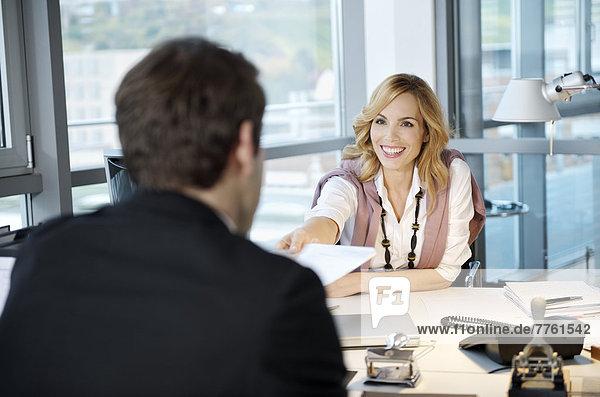 Geschäftsleute tauschen ein Papier im Büro aus