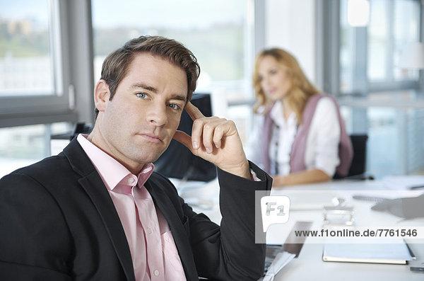 Geschäftsmann schaut in die Kamera  Frau im Hintergrund