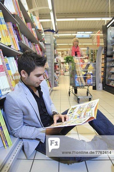 Frankreich  Supermarkt. Ein Mann  der liest.
