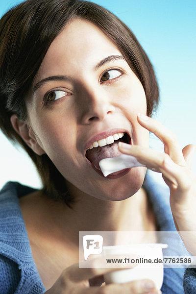 Portrait Mädchen leckt ihren Finger mit Joghurt bedeckt