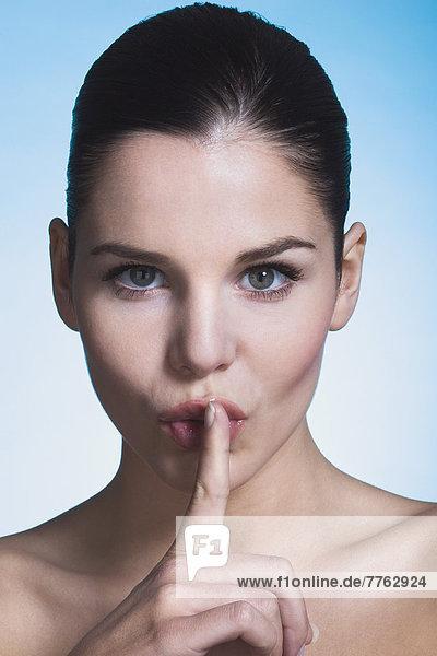 Junge Frau mit Finger auf den Lippen