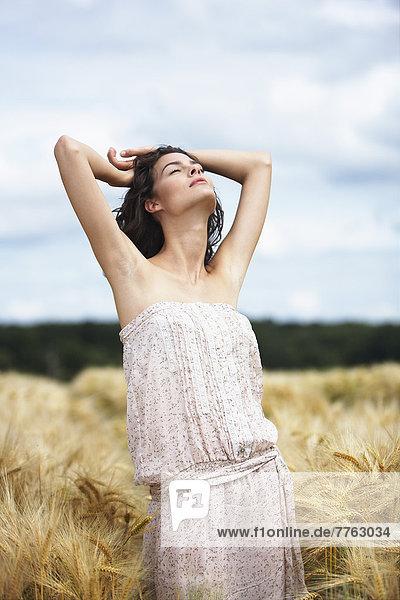 Junge Frau streckt sich im Weizenfeld