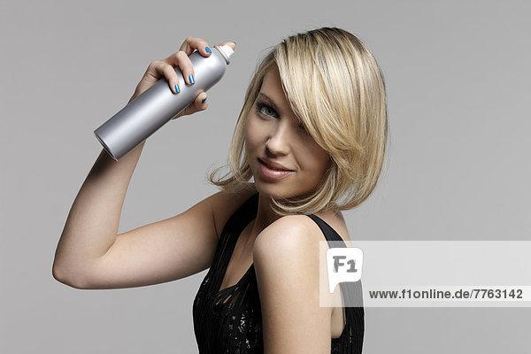 Portrait einer jungen Frau mit Haarspray