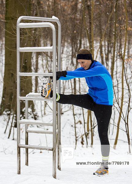 Joggerin macht Dehnungsübungen vor einem winterlichen Waldlauf