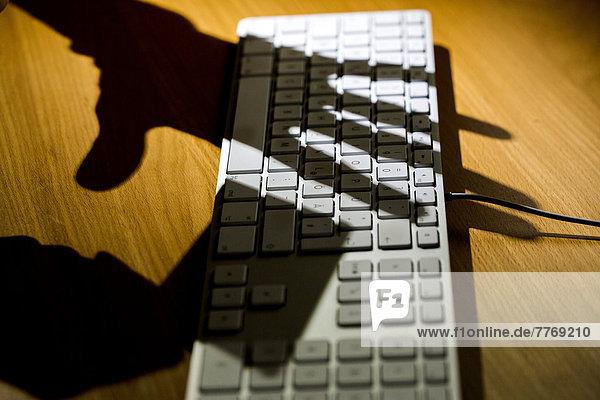 Schatten von zwei Händen über einer Computertastatur  eine Hand hält eine Kreditkarte  Symbolbild für Internetkriminalität  Datensicherheit  Computersicherheit