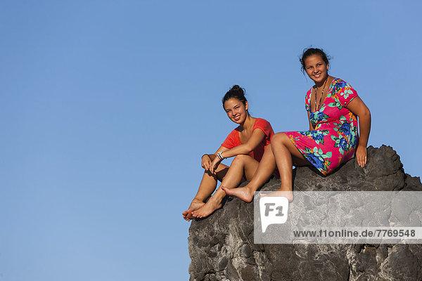 Zwei junge Frauen  etwa 15 und 19 Jahre  sitzen auf einem Stein vor blauem Himmel