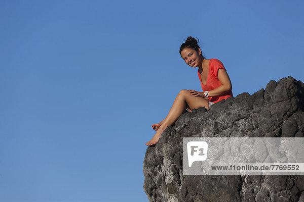 Eine junge Frau  etwa 19 Jahre  sitzt auf einem Stein vor blauem Himmel