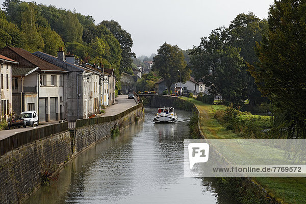 Houseboat on the Canal des Vosges  formerly Canal de l'Est  passing through a village