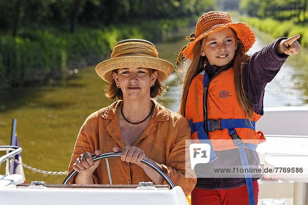 Mutter und Tochter am Steuer einer Penichette  Hausboot  auf dem Canal de Pont-de-Vaux