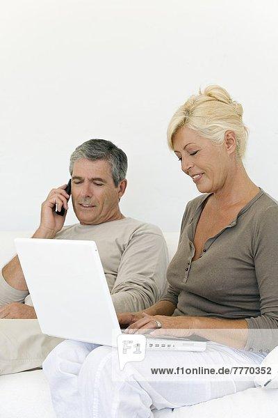 Seniorenpaar telefoniert und benutzt Laptop