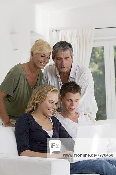Reife Paare und junge Paare zu Hause  Blick auf Laptop