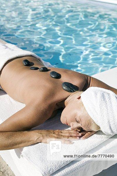 Reife Frau in der Nähe eines Pools  heiße Kieselsteine auf dem Rücken.