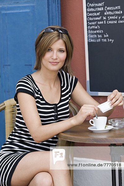 Junge Frau sitzt auf der Terrasse des Cafés