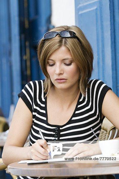 Junge Frau  die auf der Terrasse des Cafés sitzt und schreibt.