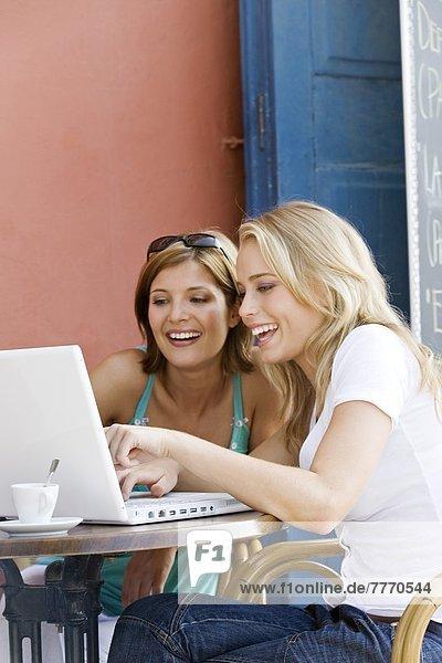 Zwei junge Frauen  die den Laptop benutzen  im Freien