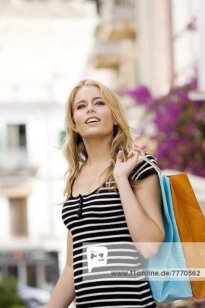 Youn Frau in der Straße hält Taschen