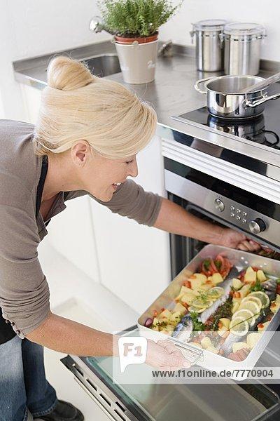 Reife Frau beim Kochen von Fisch Reife Frau beim Kochen von Fisch