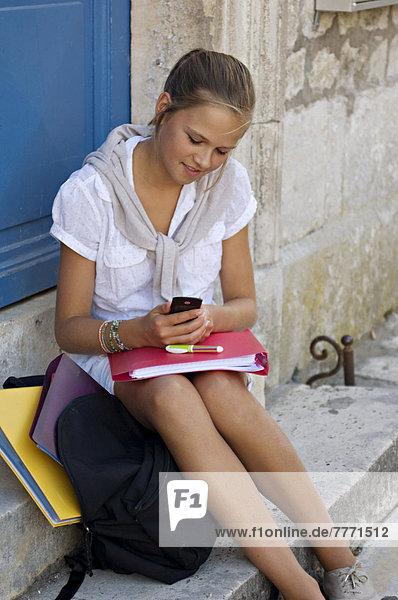 Schülerin mit Handy auf der Straße