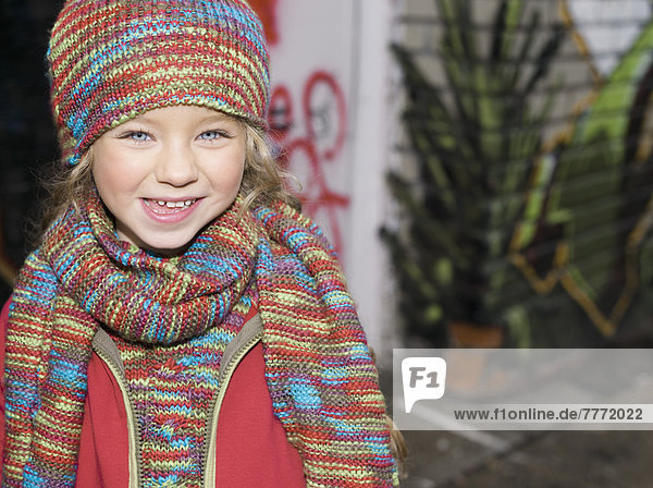 Little girl smiling in the street  wool hat and scarf