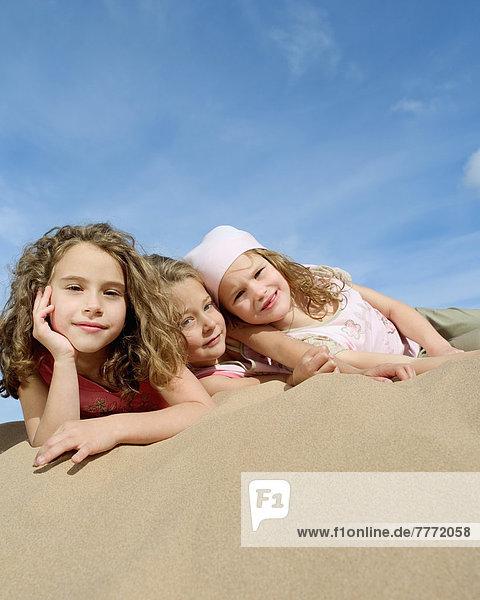 Three little girls lying on the beach