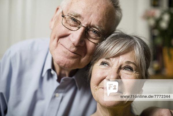Porträt eines älteren Mannes lächelnd mit wegblickender Frau