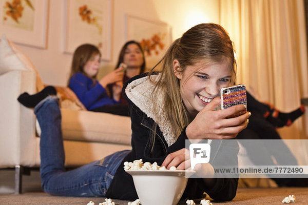 Happy girl using mobile phone while having popcorn on floor with family sitting on sofa in living room