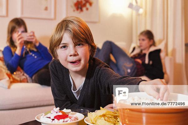 Porträt des kleinen Jungen  der Popcorn am Kaffeetisch isst  mit Schwestern im Hintergrund