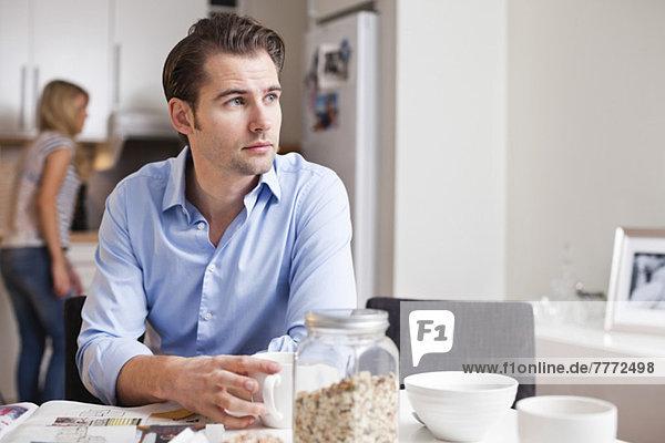 Mittlerer erwachsener Mann schaut weg  während er mit einer Frau im Hintergrund Kaffee trinkt.