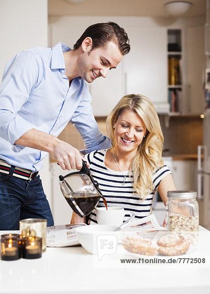 Glücklicher Mann serviert schwarzen Kaffee für die Frau am Frühstückstisch