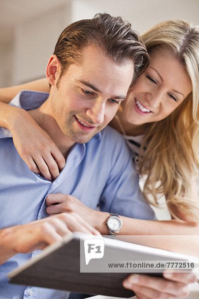 Glücklicher Mann mit digitalem Tablett und einer Frau  die ihn umarmt.