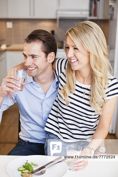 Glückliches Paar mit Wassergläsern  das am Tisch sitzt und wegguckt.
