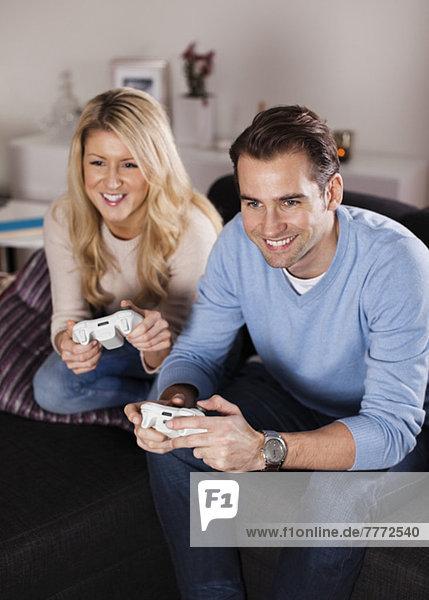 Glückliches Paar beim Spielen von Videospielen im Wohnzimmer