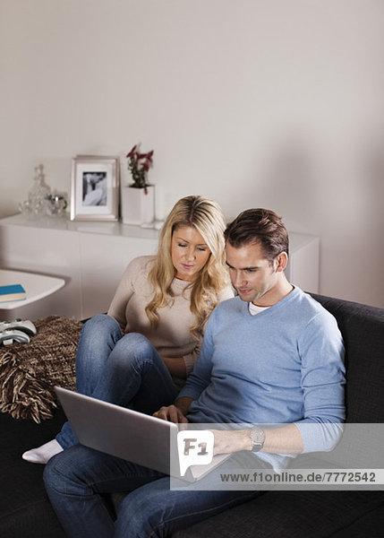 Paar mit Laptop auf Sofa im Wohnzimmer