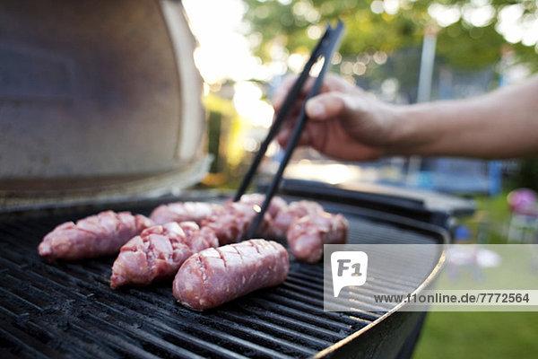 Man's Hand Grillen Fleisch auf dem Grill im Hof