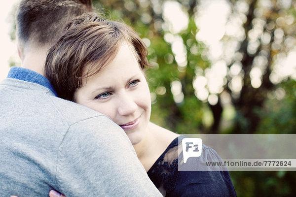Mittlere erwachsene Frau schaut weg  während sie den Mann umarmt.