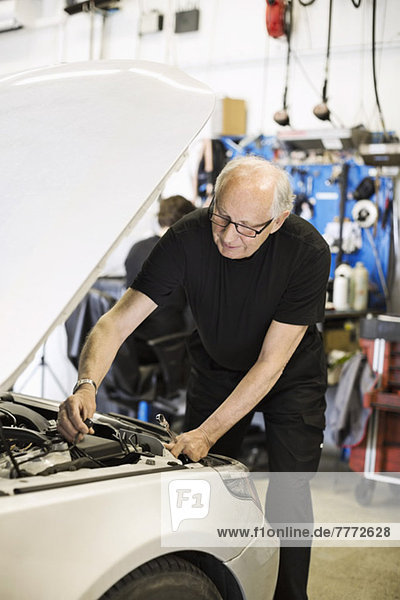 Senior male mechanic working on car engine at auto repair shop with coworker