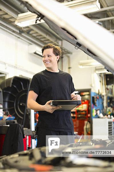 Fröhlicher junger Mechaniker mit digitalem Tablett beim Blick auf die Autowerkstatt