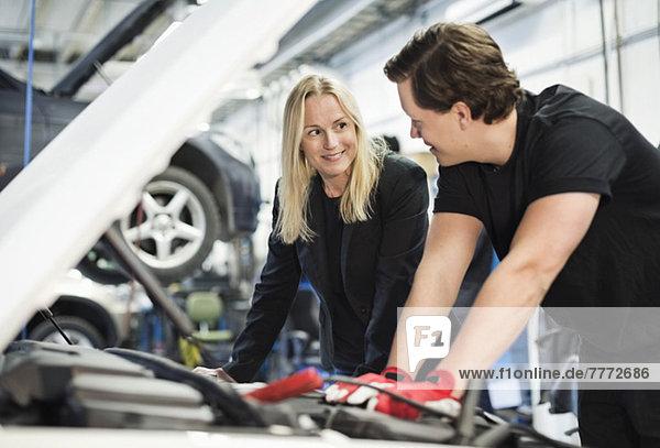 Mechaniker im Gespräch mit Kundin bei der Reparatur des Automotors in der Werkstatt