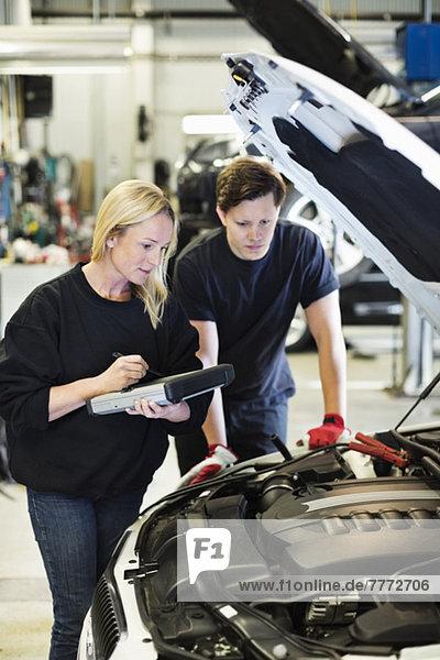 Mittlere erwachsene Mechanikerin  die ein digitales Tablett in der Hand hält  während sie mit ihrem Kollegen über den Motor des Autos diskutiert.