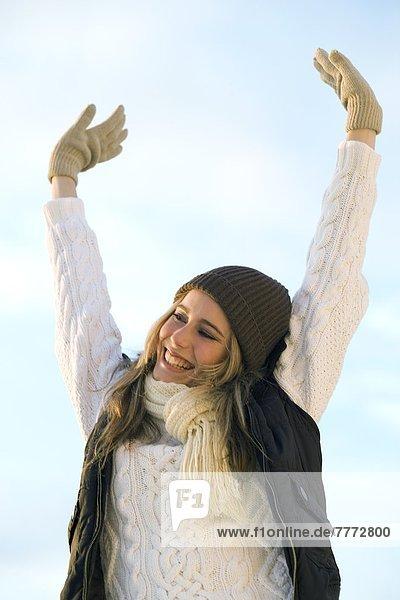 Lächelndes Teenagermädchen  mit Händen in der Luft  Winterkleidung Lächelndes Teenagermädchen, mit Händen in der Luft, Winterkleidung