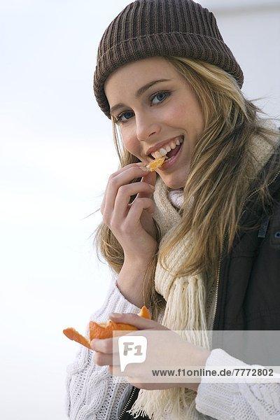 Teenagermädchen essen Clementine  Winterkleidung
