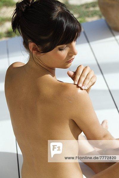 Junge nackte Frau mit Sonnencreme