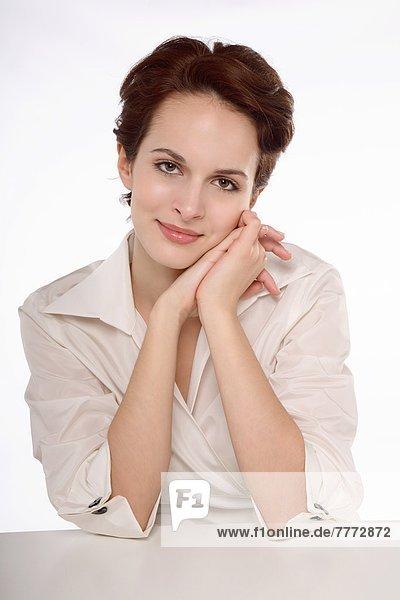 Porträt einer jungen brünetten Frau mit dem Kopf auf verbundenen Händen
